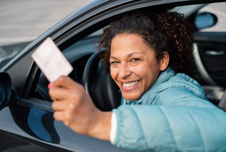 A woman with a drivers license. She's smiling, perhaps because her license has the correct gender marker on it.