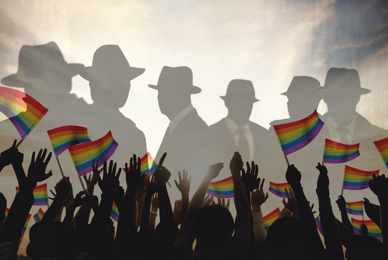 Some dudes in hats, faded in the background, and there are people holding rainbow flags.