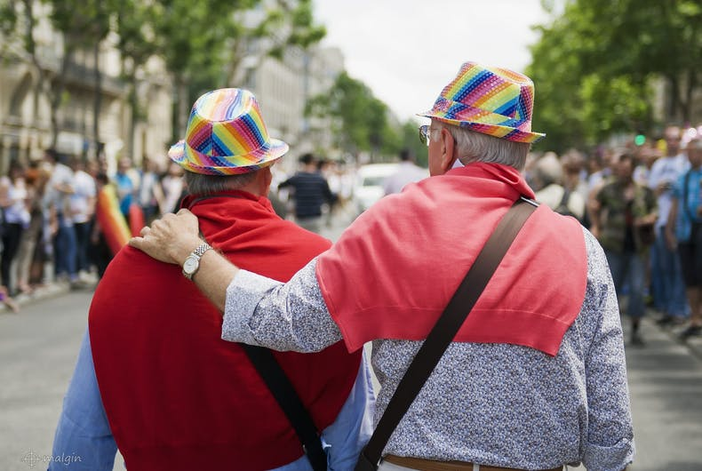An elderly gay couple in rainbow hats