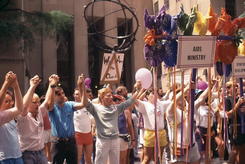 View of marchers as they stand, with raised hands clasped, in front of Rockefeller Center (across from St Patrick's Cathedral) during the New York City Pride March, June 25, 1989. The man at fore center wears a t-shirt that commemorates the 20th anniversary of the Stonewall Inn riots.