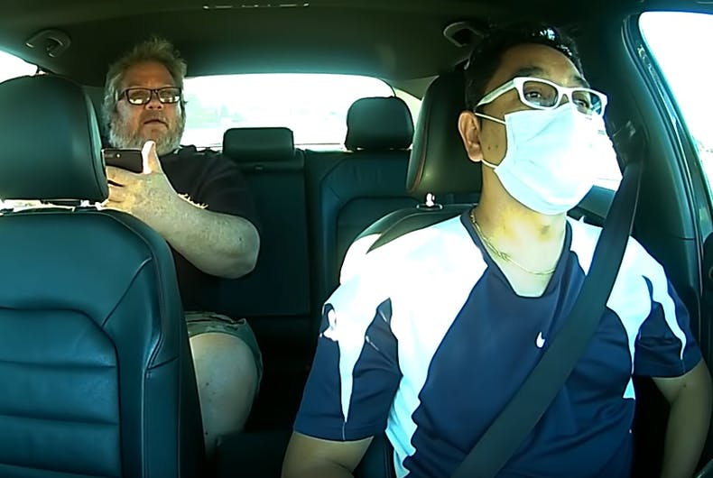 Edgar, wearing a mask, with Richard in the back of the car