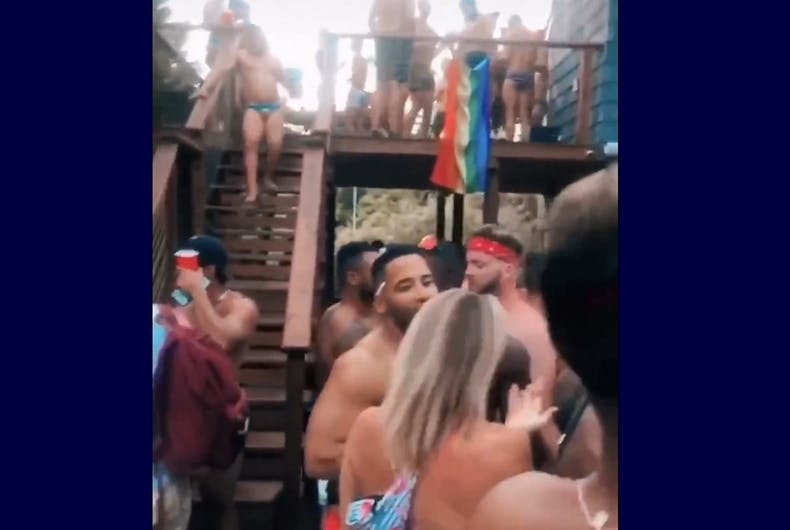 Shirtless partiers without masks and a rainbow flag in the background