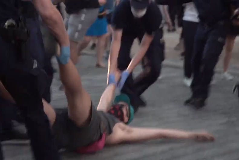 Police drag away a man protesting after an LGBTQ activist was arrested for hanging a pride flag on a statue of Jesus