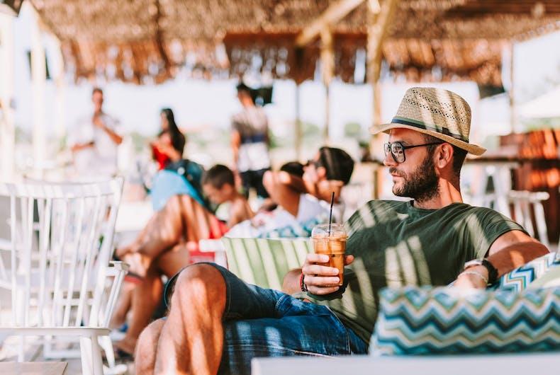 Gay guy on the beach with iced coffee